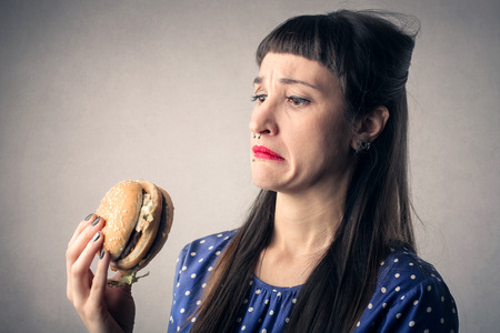 Photo pour Disgusted girl eating a hamburger - image libre de droit