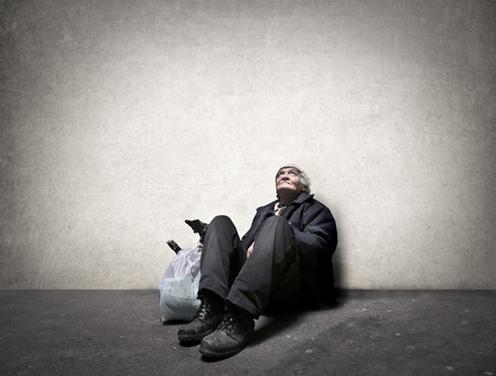 Foto de Homeless man sitting on the ground - Imagen libre de derechos