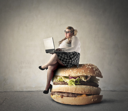 Foto per Chubby woman sitting on a hamburger - Immagine Royalty Free