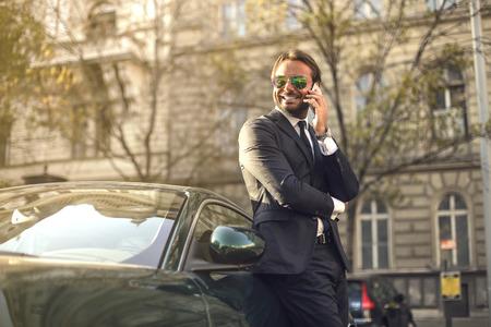 Photo pour Successful businessman standing next to his posh car - image libre de droit