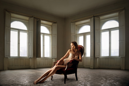 Foto de Woman sitting in a red chair in an empty room - Imagen libre de derechos