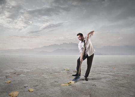 Foto de Businessman digging in search for gold - Imagen libre de derechos