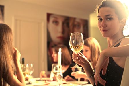 Photo pour Young woman having dinner with her friends - image libre de droit