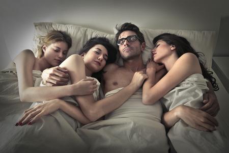 Foto de Man sleeping with three women - Imagen libre de derechos