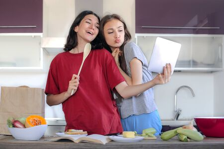 Two friends cooking in the kitchen