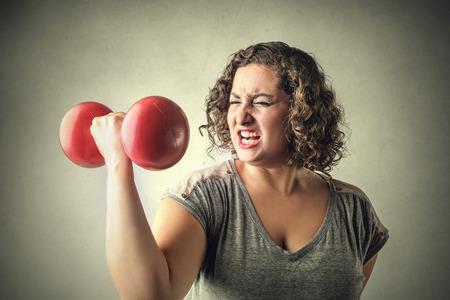 Foto de Young woman lifting weights - Imagen libre de derechos