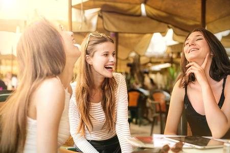 Foto de Three girls laughing while sitting at a cafe - Imagen libre de derechos