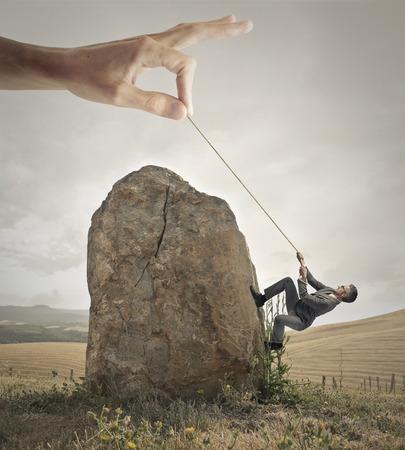 Foto de Businessman trying to climb a rock with the help of a giant hand - Imagen libre de derechos