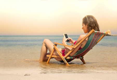 Photo for Young woman sending a text message while sitting at the beach - Royalty Free Image