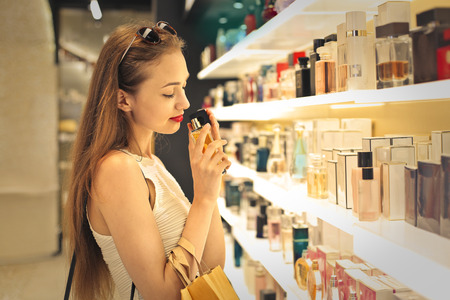 Photo for Young woman choosing a perfume - Royalty Free Image