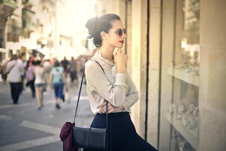 Photo pour Elegant woman looking at the window of a shop - image libre de droit