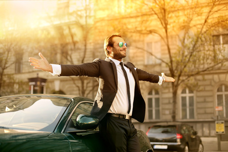 Photo pour Successful businessman standing next to his posh car - image libre de droit