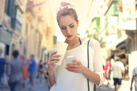 Foto de Woman with soft drink and smart phone - Imagen libre de derechos
