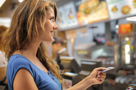 Photo for Woman paying at a fast food restaurant - Royalty Free Image