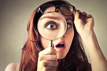 Foto de Young woman looking through magnifying glass - Imagen libre de derechos