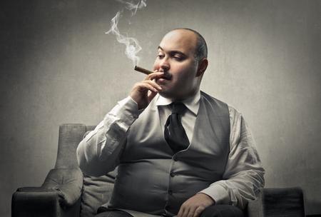 Photo pour Fat man smoking a cigar - image libre de droit