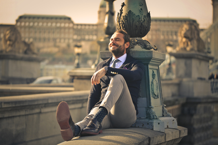 Photo pour Happy businessman sitting outdoors - image libre de droit