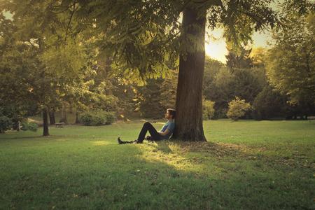 Photo pour Man sitting under a tree at the park - image libre de droit