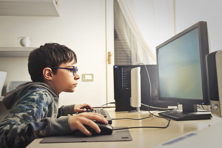 Photo pour Young boy is playing on the computer - image libre de droit
