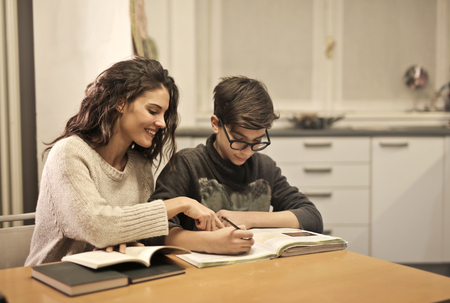 Foto de Girl helping a child with homework - Imagen libre de derechos