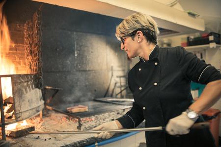 Photo pour Chef cooking with a wood oven - image libre de droit