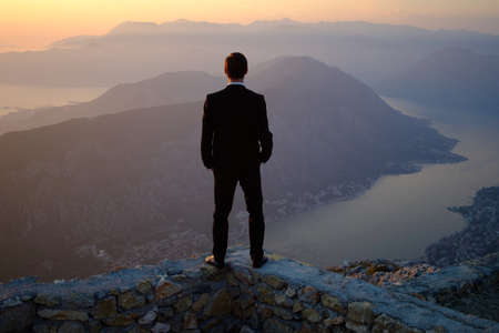 Foto de back of a young man in costume standing on a mountain at sunset. The groom or businessman looks from the top. - Imagen libre de derechos
