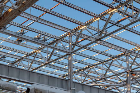Foto per Metal beams at the top of the unfinished steel structure of the building under construction, against the blue sky. - Immagine Royalty Free