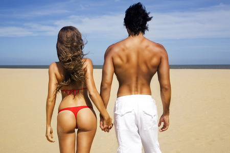 Sexy couple holding hands on the beach