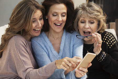 Photo for Happy group of women having fun with mobile phone outdoors - Royalty Free Image