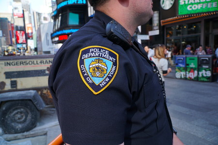 Foto für New York City - September 2016: NYPD officer stands guard in Times Square Manhattan patrol and survey public tourists looking for suspicious activity and safety threats. Police Department patch sleeve - Lizenzfreies Bild