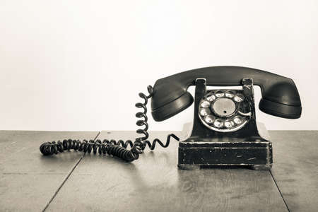 Photo pour Vintage telephone on old table sepia photo - image libre de droit