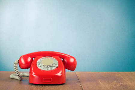 Photo pour Retro red telephone on wood table near aquamarine wall background - image libre de droit