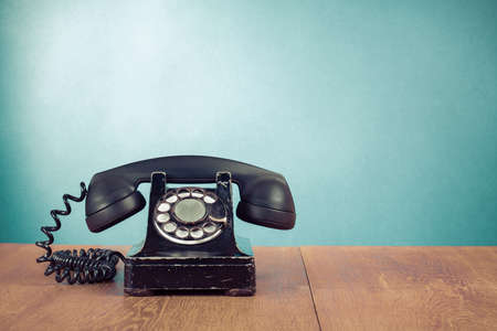 Photo for Retro telephone on table in front mint green background - Royalty Free Image