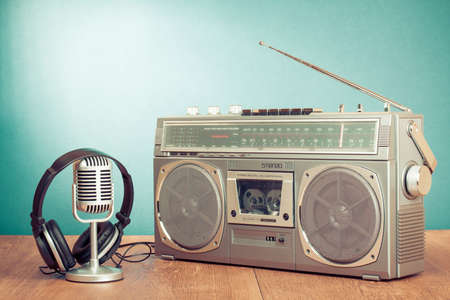 Photo for Retro radio and cassette player, headphones, microphone on table in front mint green background - Royalty Free Image