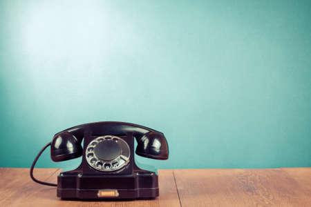 Foto de Retro black telephone on table in front mint green background - Imagen libre de derechos