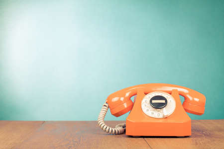 Photo for Retro orange telephone on table front mint green wall background - Royalty Free Image