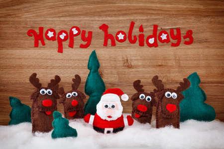 Foto de Christmas deer and Santa Claus. The concept of Xmas soft toys made of felt in the snow on a wooden background with the words - Happy Holidays - Imagen libre de derechos