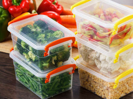 Photo for Trays with raw vegetables for freezing. Stocking up for winter storage in plastic containers - Royalty Free Image