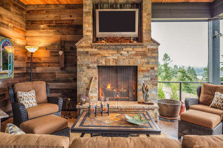Photo pour Covered Outdoor Patio Outside New Home with Couch, Chairs, TV, Fireplace, and Roaring Fire - image libre de droit
