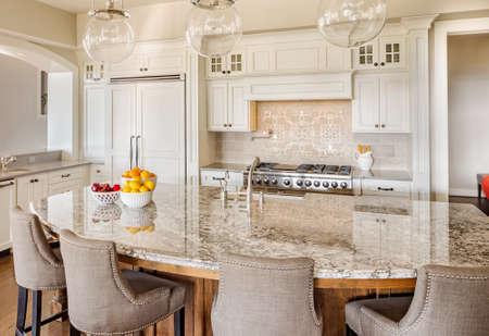 Foto de Kitchen with Island, Sink, Cabinets, and Hardwood Floors in New Luxury Home - Imagen libre de derechos
