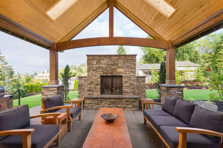 Foto de Covered patio outside luxury home with large stone fireplace, table, and couches - Imagen libre de derechos