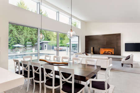 Beautiful living room and dining room with fireplace and view of outdoor patio with pool and large sliding glass doors