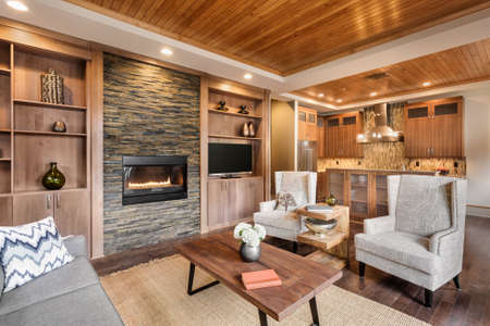 Living room interior with wood strip ceiling and view of kitchen in luxury home