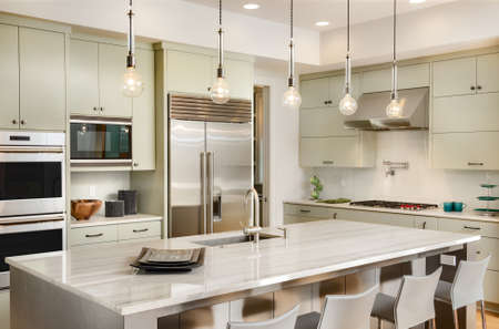 Photo pour Kitchen with Island, Sink, Cabinets, and Hardwood Floors in New Luxury Home - image libre de droit