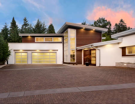 Photo pour Facade of large, luxury home with expansive driveway with colorful sunset backdrop - image libre de droit