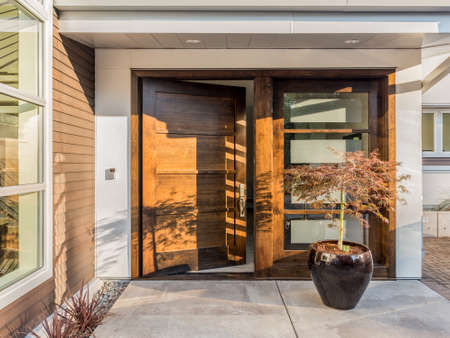 Photo pour Beautiful Wood Door as Entrance to New Luxury Home: Large and Wide Hardwood Door with Windows and Potted Plant to Right of Door in Exterior of Beautiful House. Cement Patio. Door is Slightly AjarOpen - image libre de droit
