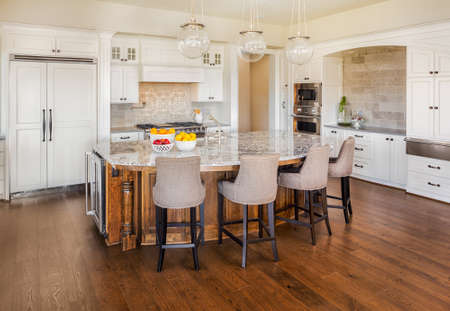 Photo pour beautiful, large kitchen interior in new luxury home with island, refrigerator, range, hood, and hardwood floors - image libre de droit