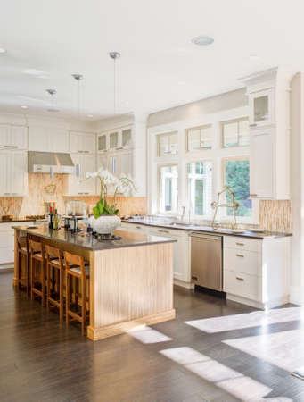Photo for kitchen interior in new luxury home with island, sink, white cabinets, and hardwood floors - Royalty Free Image