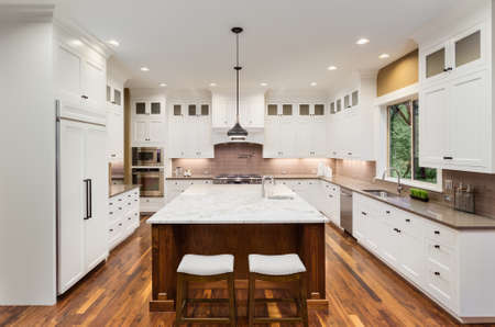Large Kitchen Interior with Island, Sink, White Cabinets, Pendant Lights, and Hardwood Floors in New Luxury Home