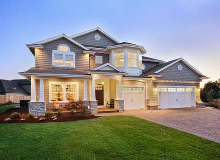 Photo pour home exterior at night/twilight with beautiful green grass three-car garage, and driveway - image libre de droit